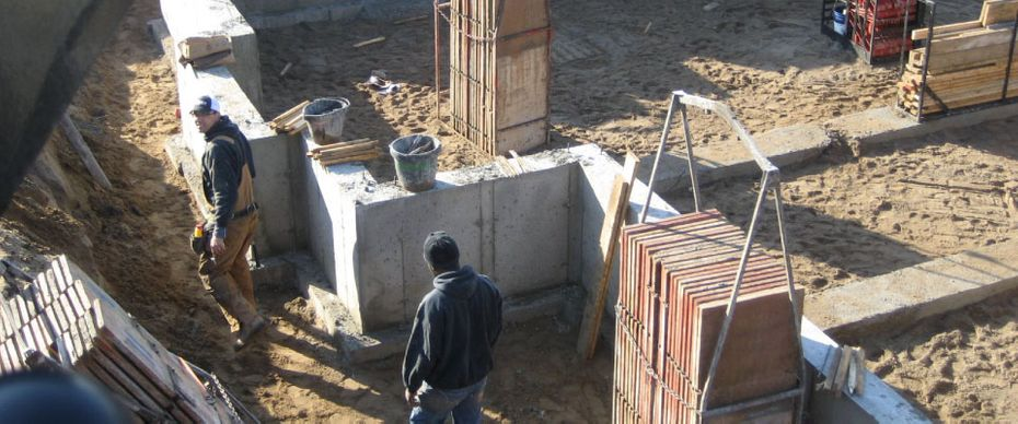 Workers Disassembling Concrete Forms for Foundation